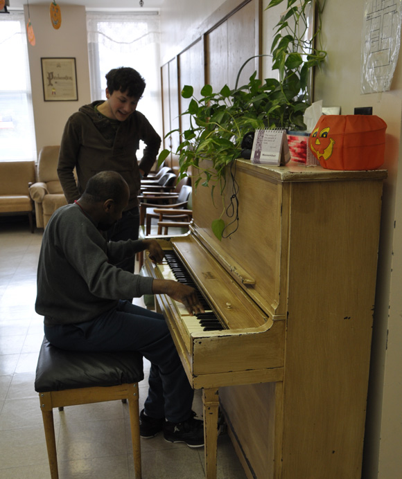 Junior Micah Program member Anthony Burchett works with a patron of Saint Elizabeth Adult Day Care Center.  Min Zhuang / Staff Photographer