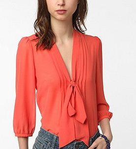 A tie-front blouse is more playful than a button up but more professional than a t-shirt. The Pins and Needles Chiffon Tie Neck Tunic in orange offers the perfect mix (Photo courtesy of Urban Outfitters.com).