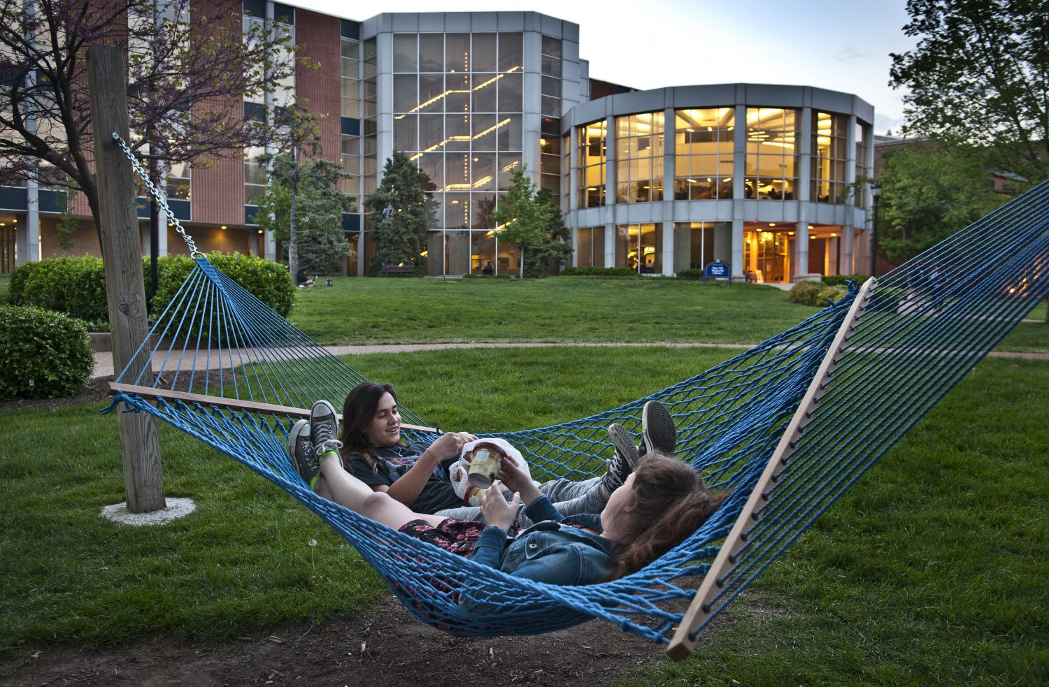 Twilight+downtime%3A+Two+students+eat+ice+cream+on+one+of+campus%E2%80%99s+signature+blue+hammocks.+Students+have+supplemented+the+hammock+shortage+with+a+portable+alternative.+Courtesy+Michelle+Peltier