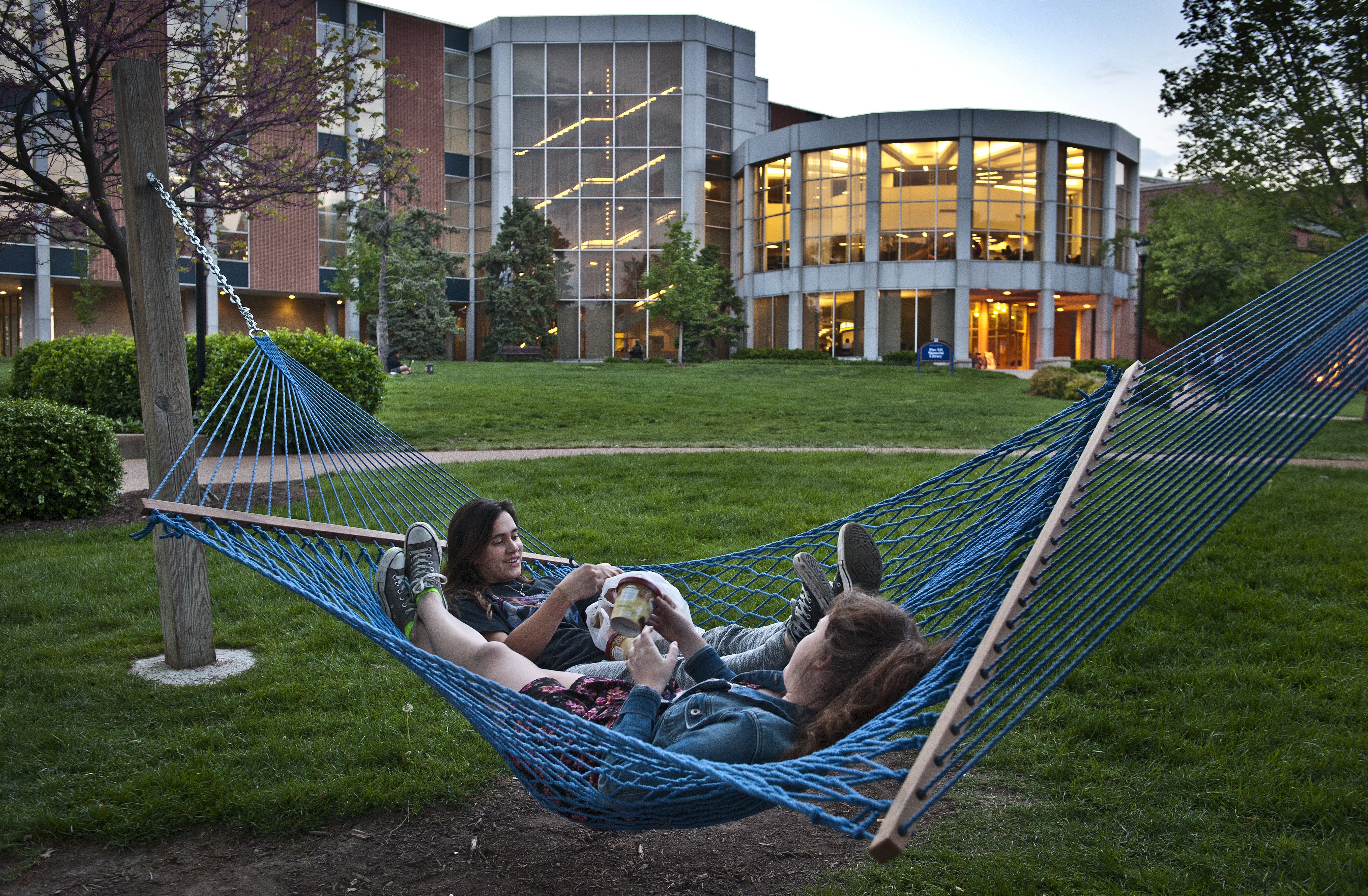 Twilight downtime: Two students eat ice cream on one of campus's signature blue hammocks. Students have supplemented the hammock shortage with a portable alternative. Courtesy Michelle Peltier