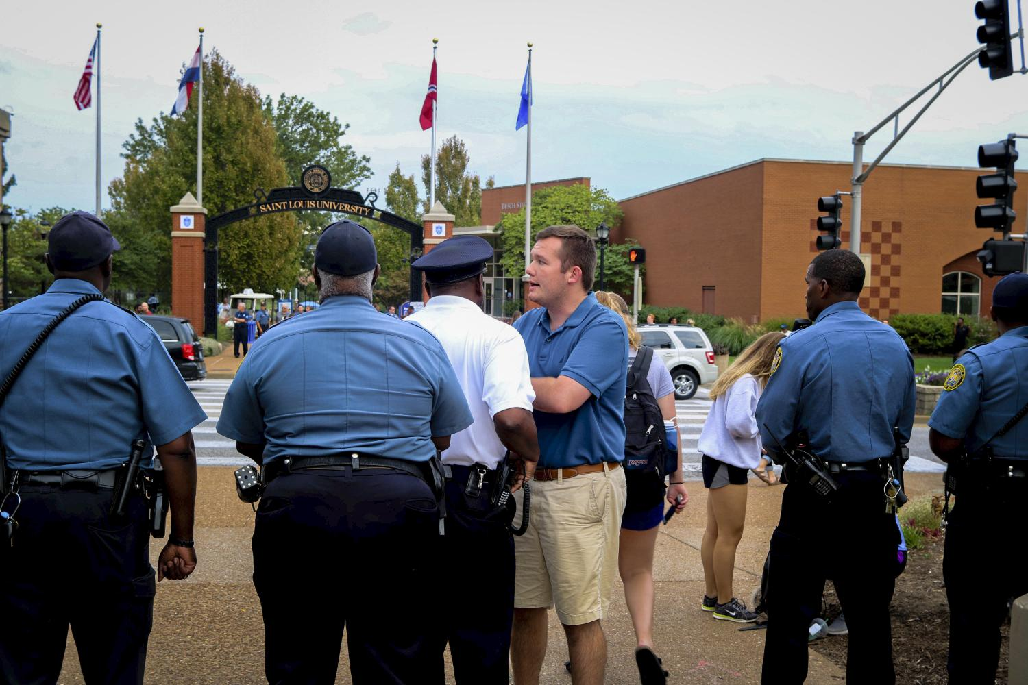 SLU student government president Dan Carter speaks with officers from the University's Department of Public Safety after a large group of protesters continued their march past campus along Grand Blvd.