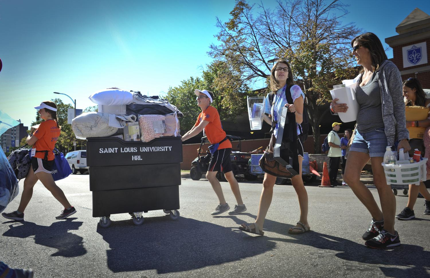 Oriflamme members and new SLU families cross Laclede to Grand and Griesedieck residence halls.