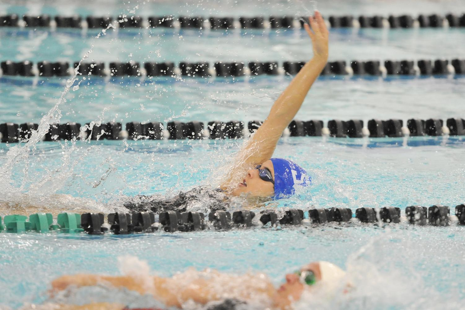 Senior Riley Kirby securing the win in the 100 meter backstroke in the home opener.