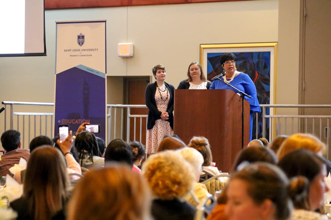 Heather Brock (Award Committee Chair) and Kellisa Lyn Fiala (President) stand on stage behind Woman of the Year Regina Walton. (Emma Carmody / The University News)