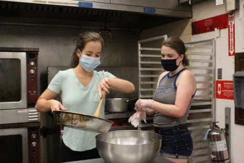 Claire Bartusch and Julia Duncan transferring ingredients from a pan into a bowl.